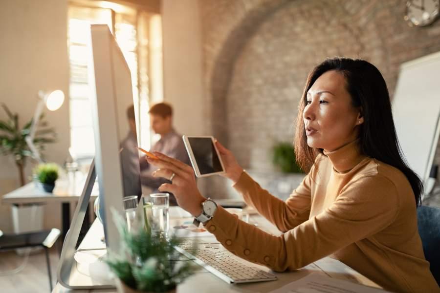 Geschäftsfrau sitzt an Schreibtisch und analysiert Daten auf Monitorscreen im Abgleich mit Smartphone