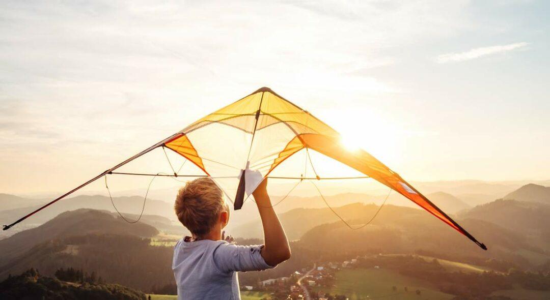 Junge startet Drachen in den Sonnenuntergang