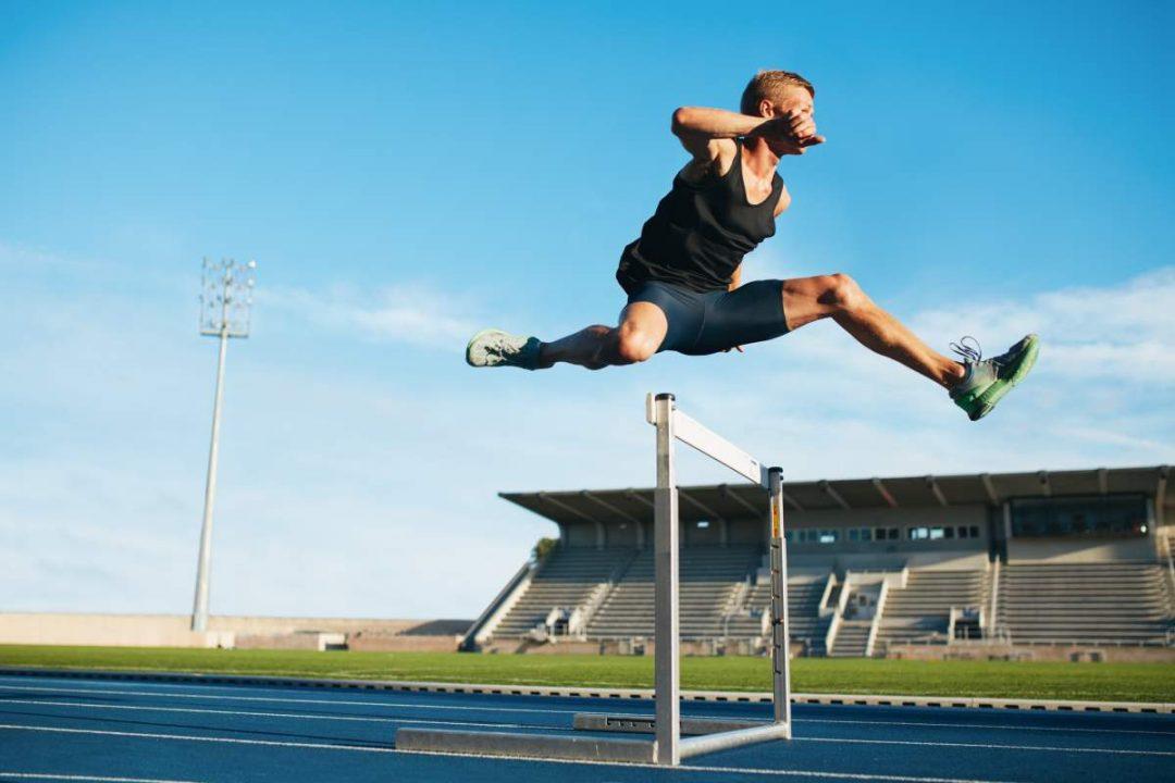 Hürdenläufer springt über Hindernis auf einer Laufstrecke im Stadion