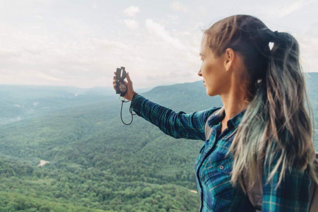 Frau mit Kompass orientiert sich in Landschaft
