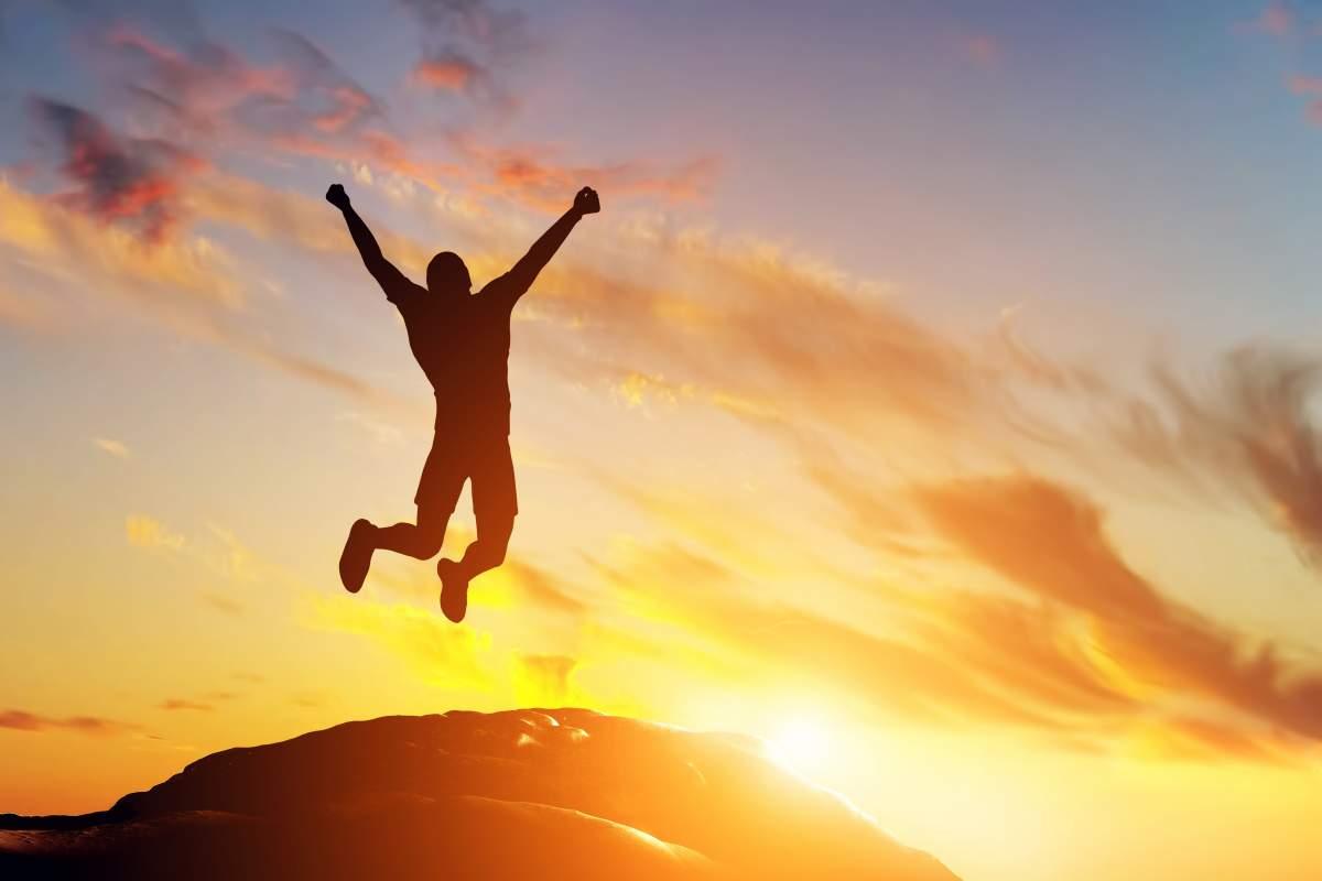 Silhouette einer Person, die in der Natur bei Sonnenuntergang vor Glück in die Luft springt